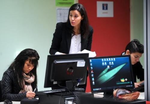 An instructor teaches a computer course for students who have dropped out of school in Saint-Andre-lez-Lille on January 7, 2014