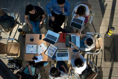 A photo shows people sit around laptop computers at a cafe in Beijing on May 29, 2013
