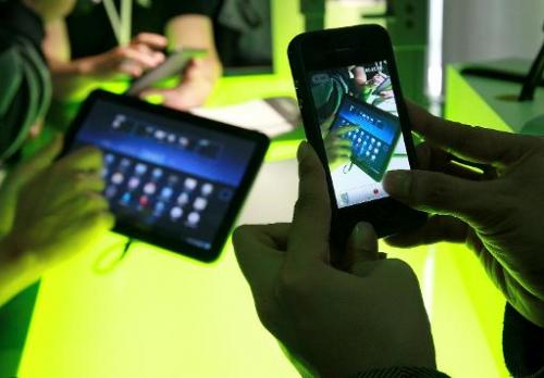 A reporter uses a cell phone to take a photograph of Google Android 3.0 Honeycomb OS being used on a Motorola Xoon tablet during
