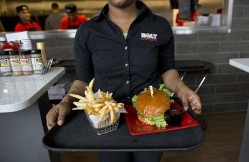 A server carries a tray with a hamburger and french fries at Bolt Burgers in Washington, DC, February 25, 2014