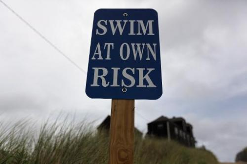 "A sign reads, ""Swim at Own Risk"" at Ballston Beach on Cape Cod on August 12, 2012 in Truro, Massachusetts"