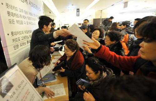 A South Korean customer receives an application form to cancel her credit card at a branch of Lotte Card in Seoul on January 22,