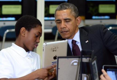 A student shows US President Barack Obama how he is working to create an ebook with an iPad in a classroom at Buck Lodge Middle
