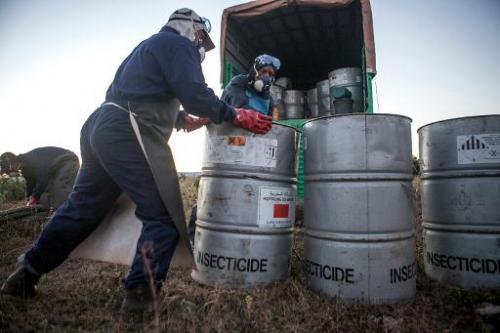 A team prepares pesticide containers, which will be attached to a helicopter, in Tsiroanomandidy, Madagascar on May 7, 2014