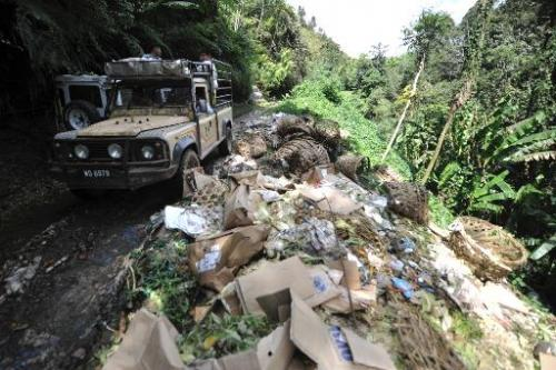 A truck passes piles of rubbish in the Cameron Highlands, Malaysia, on November 19, 2013