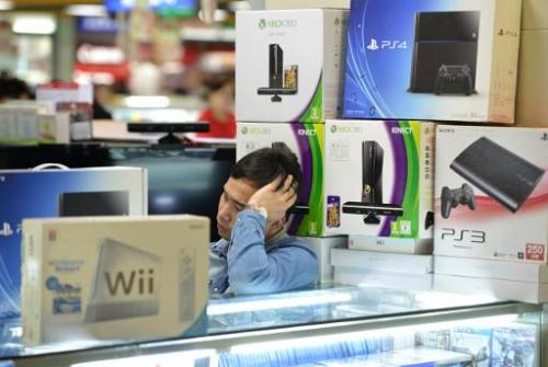 A vendor sells game consoles including Xbox One and Sony's PS4, which they say enter China through unofficial channels, in a maj