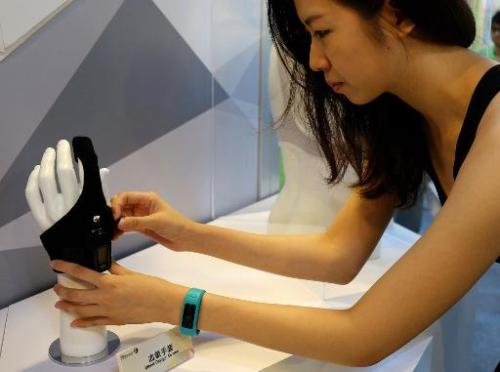 A woman adjusts an Oximetry glove designed by Taiwan Textile Research Institute (TTRI) during the Computex tech show in Taipei o