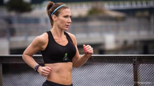 A woman jogs wearing the Sensoria Fitness bra, made by Heapsylon