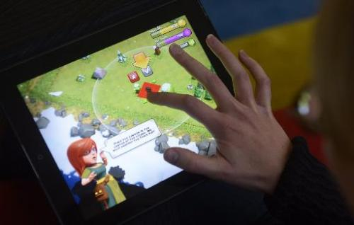 A woman plays the Clash of Clans game of Finnish computer game maker Supercell on a tablet computer on December 14, 2012 in Hels