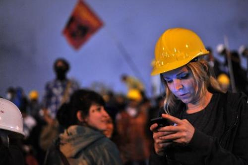 A woman uses a mobile phone to read the news on social media at a midnight demonstration in Taksim Gezi Park on June 13, 2013