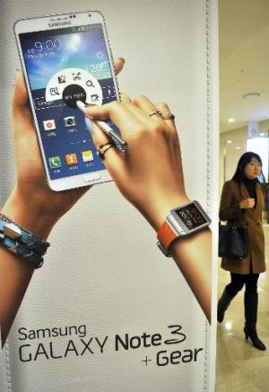 A woman walks past a sign board advertising Samsung Electronics' Galaxy Note 3 smartphone in Seoul on January 7, 2014