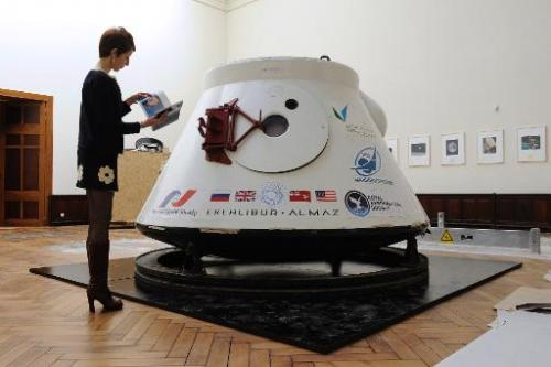 A women stands next to Soviet space capsule Vozvrashchayemi, on April 23, 2014, in Brussels, ahead of its auction on May 7, 2014