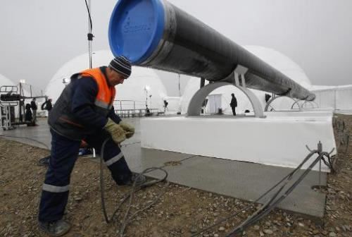 A worker checks wires in front a gas pipe line section before a ceremony to launch the construction of South Stream gas pipeline