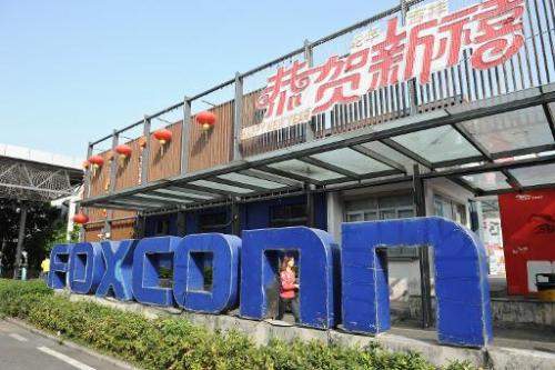 A young woman walking past a Foxconn recruitment point in Shenzhen, south China's Guangdong province on February 22, 2013