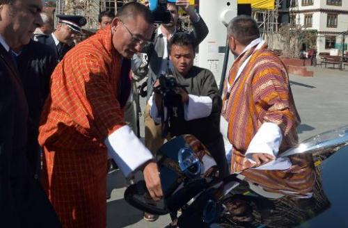Bhutanese Prime Minister Tshering Tobgay (2nd L), watched by Nissan Motor CEO Carlos Ghosn (L), plugs in a receptacle to charge