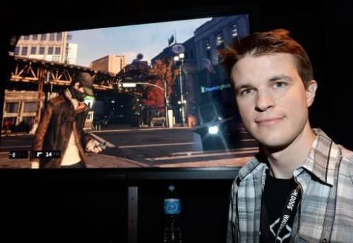 "Canadian Ubisoft developer Dominic Guay next to a screen shot from the Ubisoft game ""Watch Dogs"" at the E3 video game"