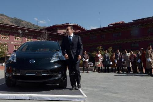 Carlos Ghosn stands next to a Nissan Leaf electric car in Thimphu on February 21, 2014