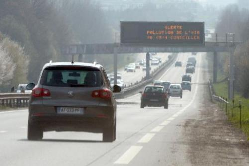 "Cars drive past a traffic board reading ""Warning air pollution 90 km /h recommended"" near Rennes, western France on Ma"
