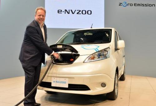 Chief planning officer for Japan's auto giant Nissan, Andy Palmer, poses with the company's new commercial electric vehicle &quo