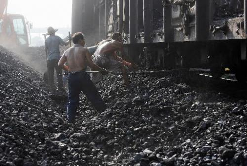 Chinese miners unload coal from a train in Hefei, in eastern China's Anhui province on August 4, 2010