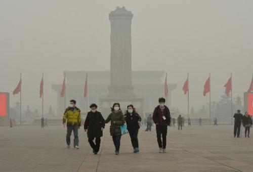 Chinese tourists wearing face masks visit Tiananmen Square as heavy air pollution continues to shroud Beijing on February 26, 20