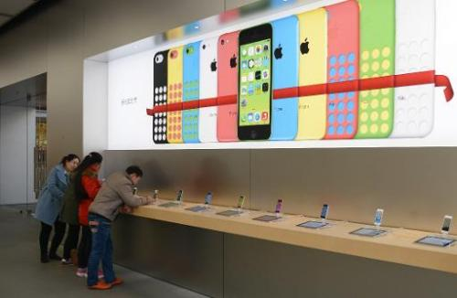 Customers looking at iPhones in an Apple store in Shanghai, on January 14, 2014