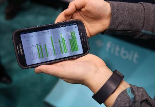 Data collected from the Fitbit Force is displayed on a smartphone in the Fitbit booth at the 2014 International CES at the Las V