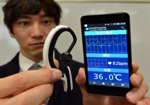 """Engineer from Japanese machinery maker NS West shows the """"Earclip-type Wearable PC"""" equipped with sensors such as a pu"""