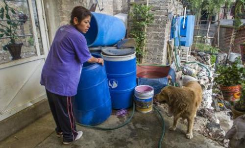 Fabiola Vargas prepares to fill a container with water in the community of Tehuixtitla in southern Mexico City on April 29, 2014