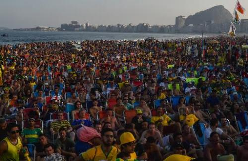 Fans watch a live broadcast of the World Cup match between Brazil and Mexico at Copacabana beach in Rio de Janeiro on June 17, 2