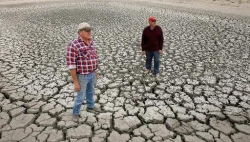 Farmer Marshall Rodda (L) and Gilbert Fryatt (R) stand in an empty dam during the country's worst drought in a century in the Au