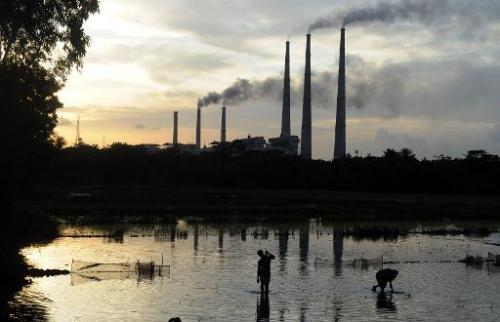Farmworkers prepare a flooded field for rice-growing as the chimneys of the Kolaghat Thermal Power Plant loom the background in
