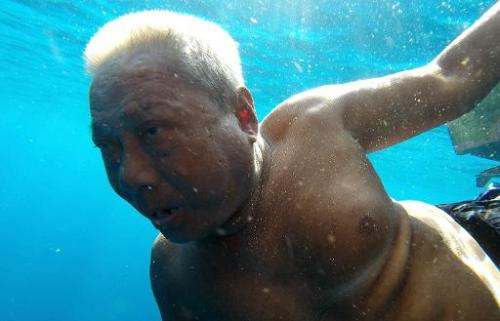 Fish listener Harun Muhammad clings onto his fishing boat at sea near Setiu lagoons on June 8, 2014