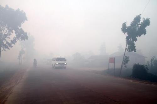 Haze from forest fires blankets a road in Dumai in Indonesia's Sumatra island on June 22, 2014