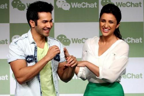 Indian Bollywood actors Varun Dhawan (L) and Parineeti Chopra joke during the launch of the WeChat messenger application in Mumb