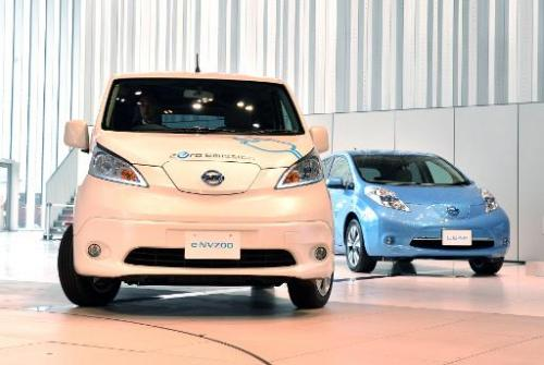 "Japanese auto maker Nissan Motor's electric vehicles ""e-NV200"" (L) and ""Leaf"" are pictured on June 9, 2014 a"