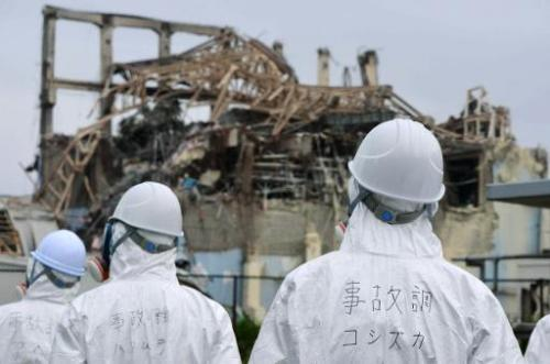 Japanese inspectors look at the damaged building housing reactor number three at the Fukushima nuclear facility at Okuma, on Jun