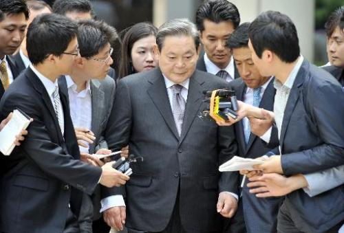 Lee Kun-Hee (centre), former Samsung Group chairman, leaves after his trial at the Seoul High Court in Seoul on August 14, 2009