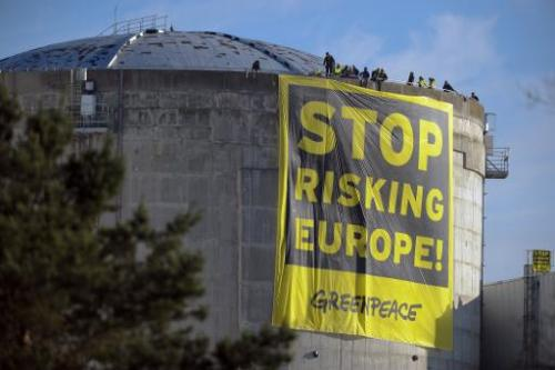 "Militants of Greenpeace deploy a banner reading ""Stop risking Europe"" on a reactor of the nuclear power plant of Fesse"