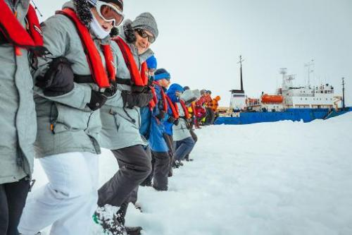 Passengers link arms and stamp out a helicopter landing site on the ice near the MV Akademik Shokalskiy (back R), still stuck in
