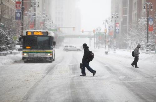 Pedestrians cross the street in Detroit, Michigan, as huge areas of North America deal with record-breaking freezing weather Jan