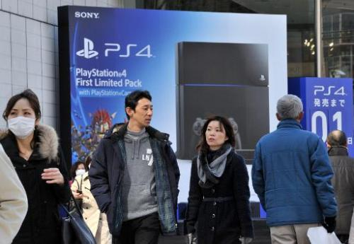 People pass before a large advertisement board of Sony Computer Entertainment's PlayStation 4 video game console at Tokyo's shop
