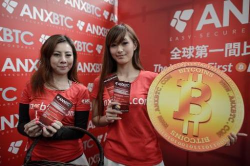Promotion girls pose during the opening ceremony of the city's first bitcoin retail shop in Hong Kong on February 28, 2014