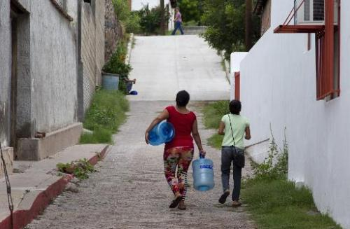 Residents go to collect drinking water in the Arizpe community, Sonora state of Mexico, on August 12, 2014