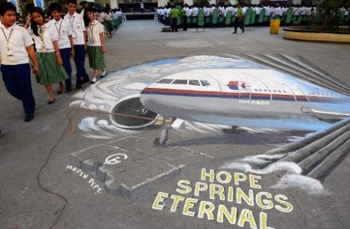 Students walk past a giant mural featuring missing Malaysia Airlines flight MH370 displayed on the grounds of their school in Ma