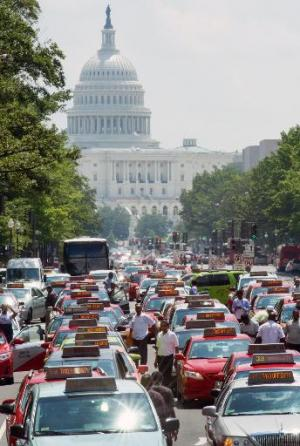 Taxi drivers park their cars and honk their horns in protest of ride sharing services like Uber on June 25, 2014, in Washington,
