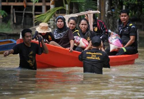 Thai villagers take a boat to get government food packs during floods in the southern Narathiwat province on December 6, 2013