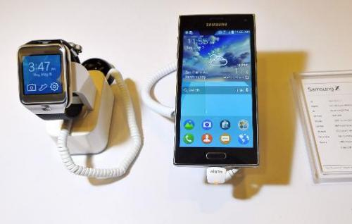 The new Samsung Z910F smartphone (R) and the SM-R380 smartwatch are seen on display at the Tizen Developer Conference in San Fra