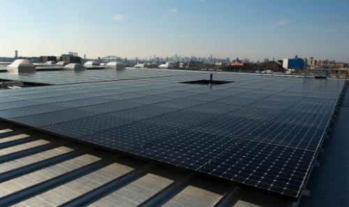 The rooftop of Jetro Restaurant Depot in the Bronx, with a view of Manhattan in the distance,  is covered with solar panels on J