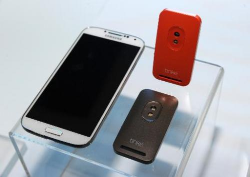 The Tinké connected health monitor by Zensorium is displayed beside an Android smartphone to which it can link via Bluetooth at